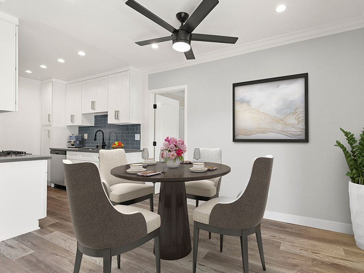 Dining room with hardwood floors, ceiling fan, and view of modern kicthen.