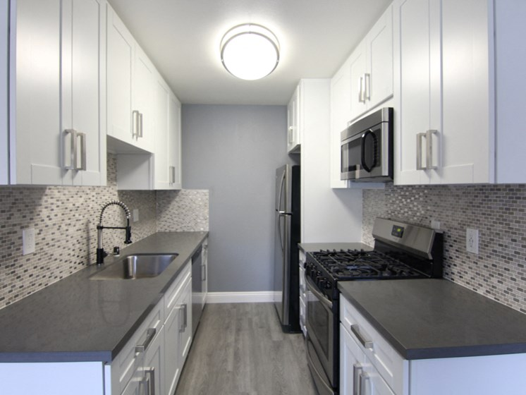 Kitchen with quartz stone counters and stainless steel microwave, oven, fridge, and fixtures.