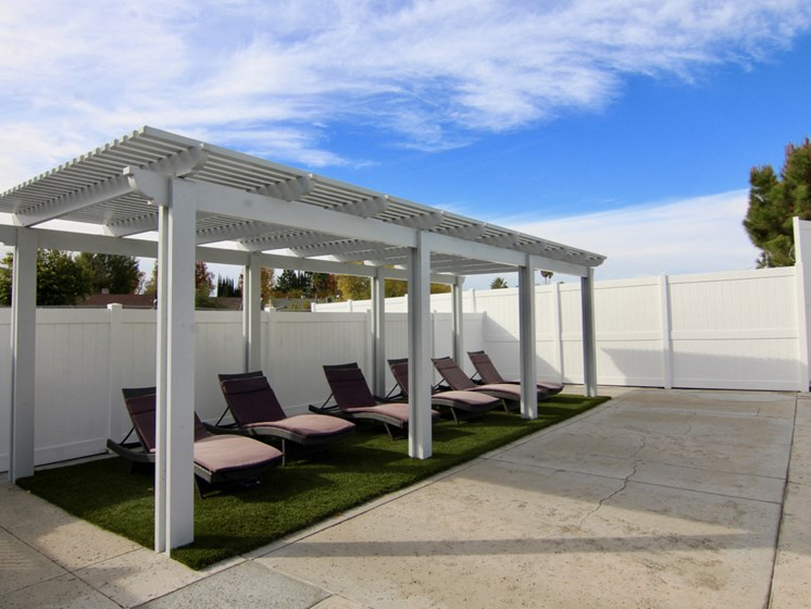 Pool lounging area with gazebo room for at least 5 people.