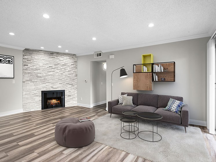 Living room with decorative stone wall, fireplace, and hardwood floors.