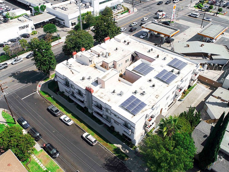Aerial drone photo of Magnolia Terrace showing solar panels and energy-efficient white roof.
