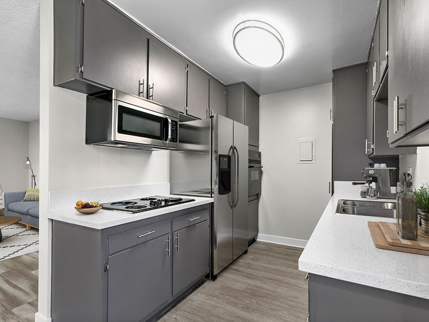 Spacious kitchen with stainless steel fridge, oven, and microwave.