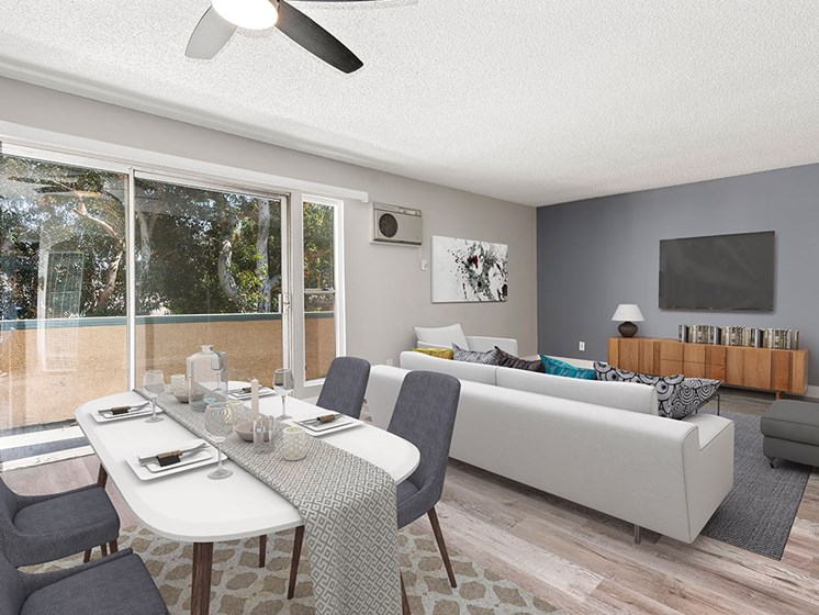 Hardwood floored dining room with ceiling fan and view of living room and private balcony.