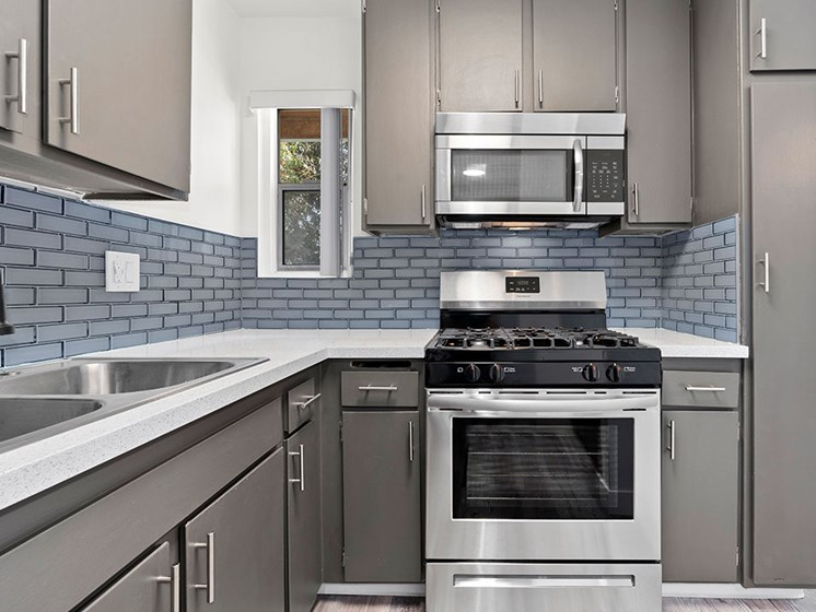 Blue tiled kitchen with stainless steel fridge, oven, and microwave.
