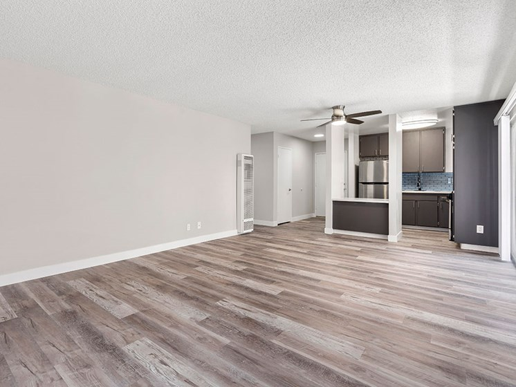 Hardwood floored living room with view of dining area and kitchen.