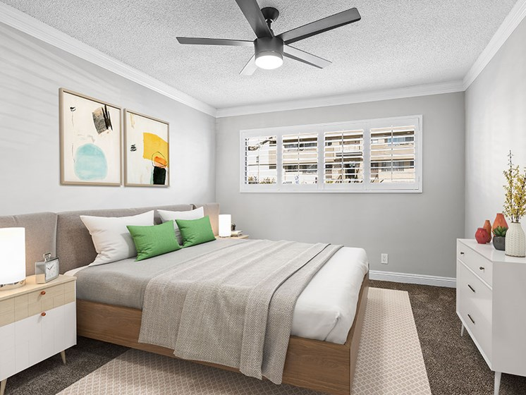 Carpeted bedroom with ceiling fan.