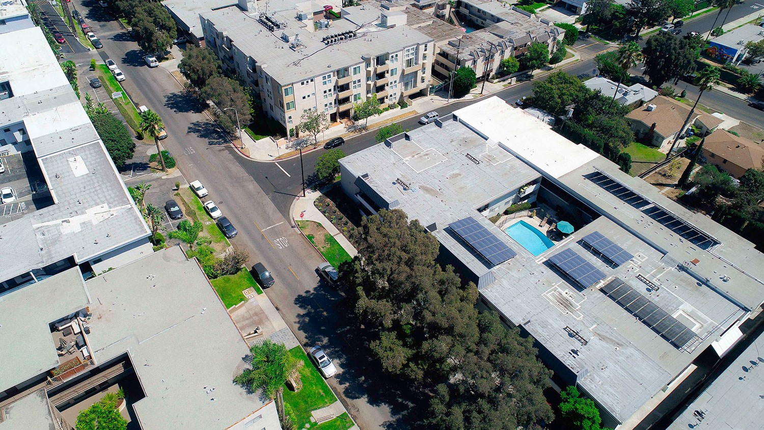 Aerial drone image of Rose Apartments and courtyard with pool.