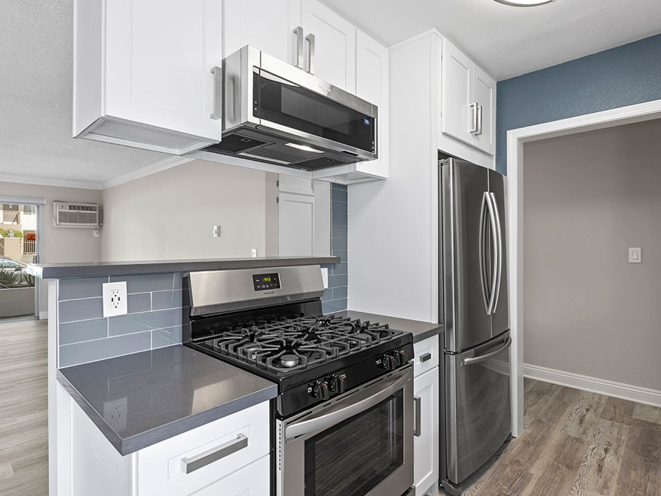 Kitchen with blue tile backsplash and stainless steel Stove, Oven, and fixtures.