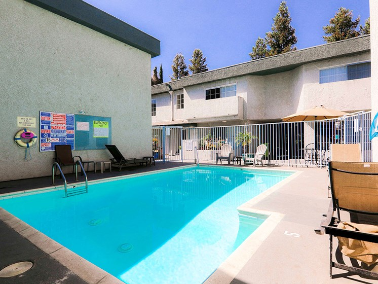 Community pool with chairs and lounging area.