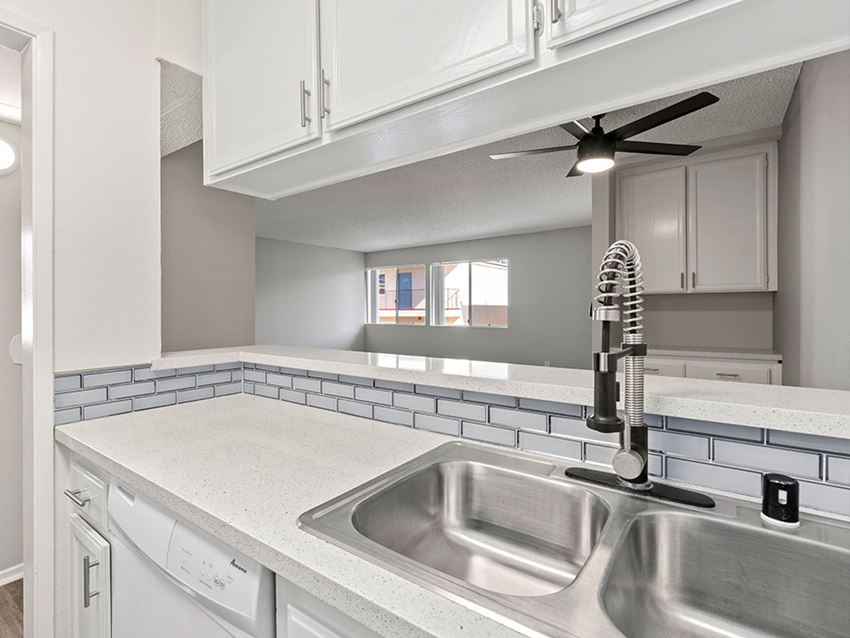White tiled kitchen with stainless steel farmhouse style sink.