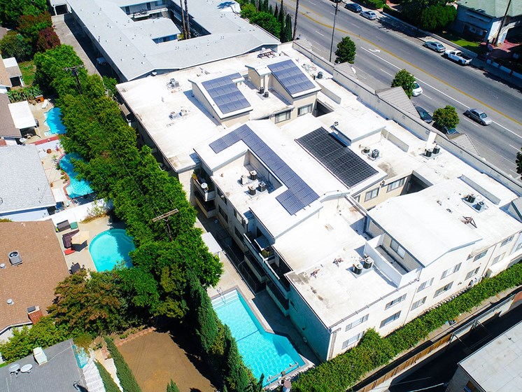 Aerial drone picture of the building showing solar panels and white energy-efficient roof.