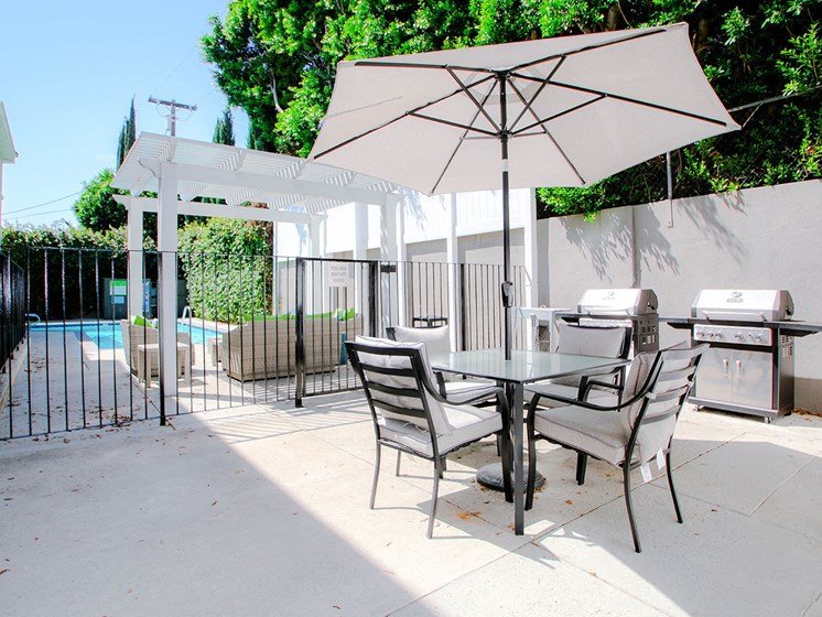 Courtyard barbecue and seating area with umbrella.
