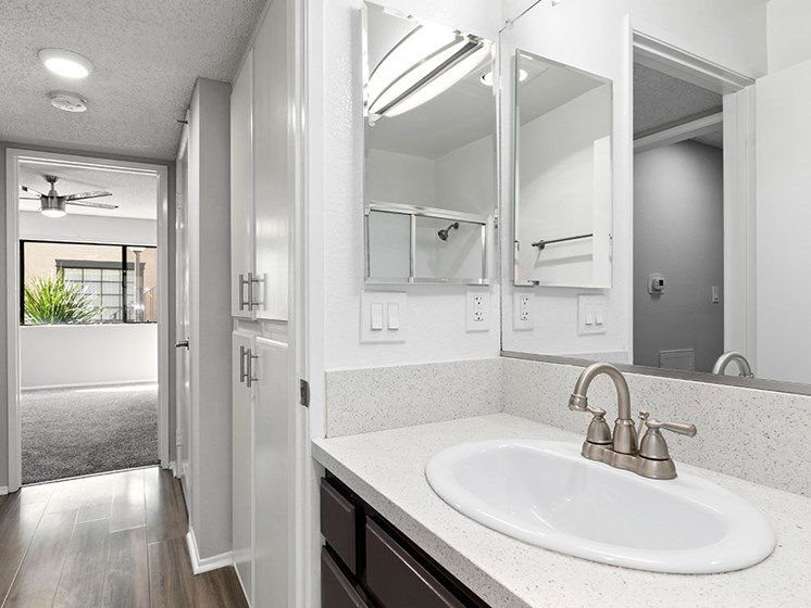 Modern styled bathroom with view of hall and bedroom.