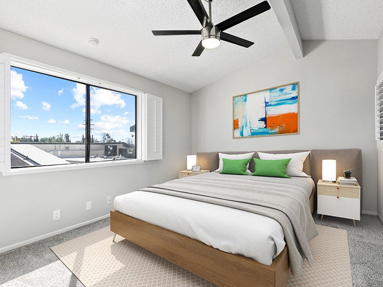 Carpeted bedroom with ceiling fan and large window for natural light.