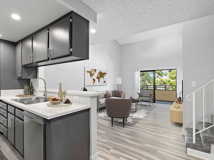 Spacious and open kitchen area with view of living room and balcony.