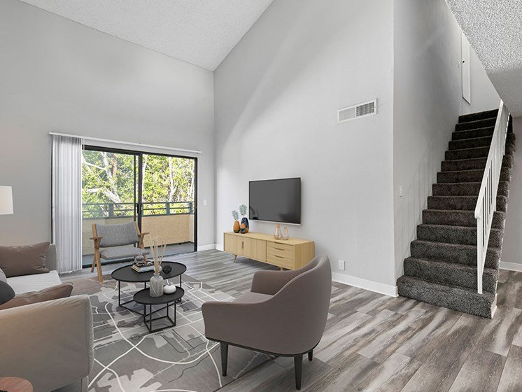 Hardwood floor living room with view of loft staircase.