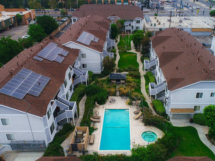 Aerial view of the courtyard, pool, jacuzzi, and solar panels.