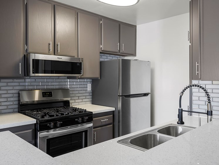 Tiled kitchen with stainless steel microwave, oven, and fridge.