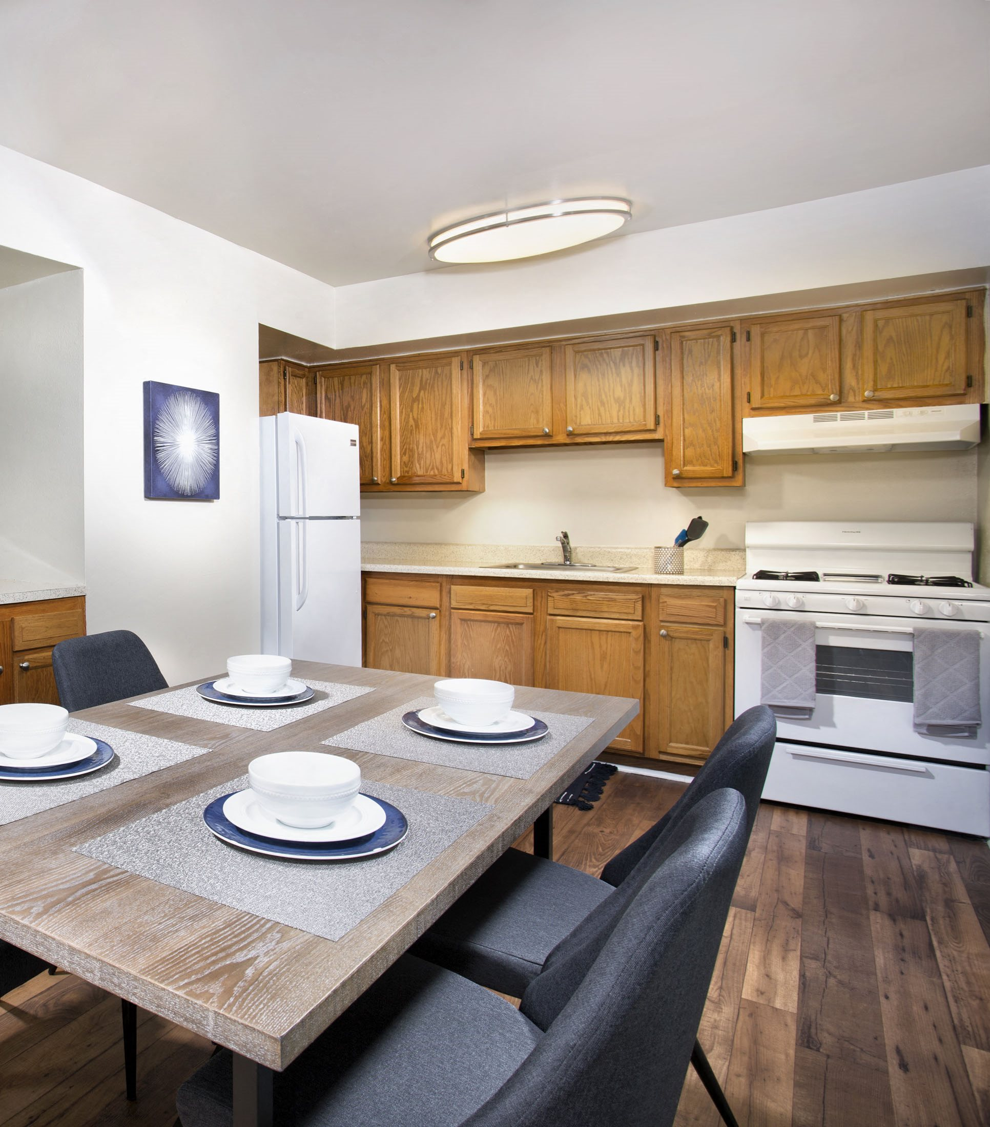 kitchen at Oaks at Park South apartments in Oxon Hill with plan flooring, white appliances, brown wood cabinets and dining table with four place settings