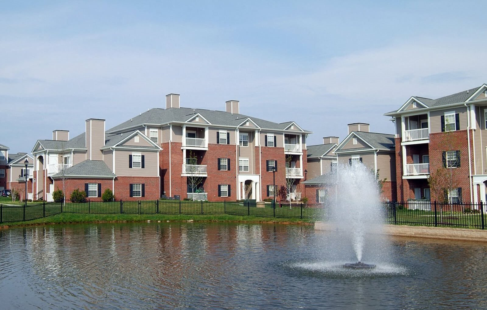 Pond with fountain and buildings at The Belvedere Apartments in Richmond, VA