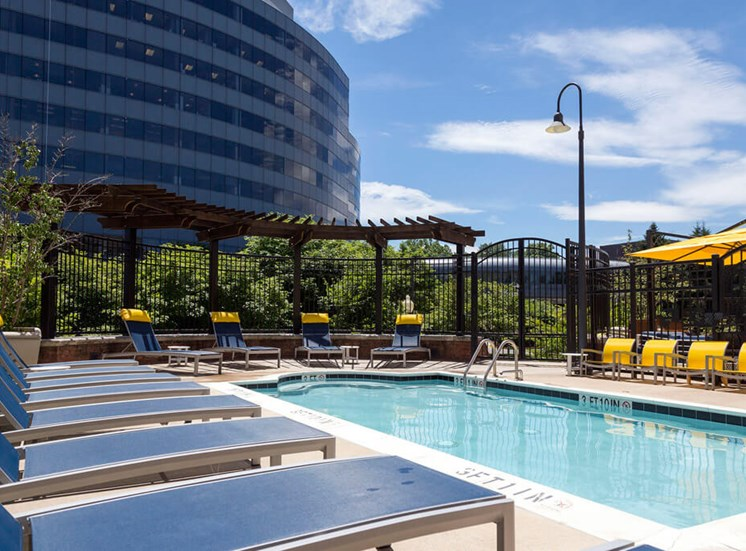 Swimming pool and lounge chairs at Dwell Vienna Metro Apartments in Fairfax, VA