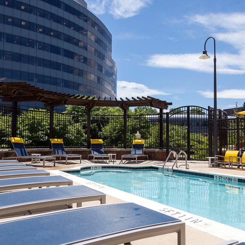 Swimming pool and lounge chairs Dwell Vienna Metro Apartments in Fairfax, VA