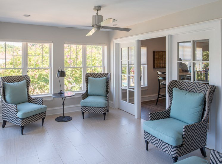 Resident clubhouse with sun-room featuring cozy chairs, multiple windows, and ceiling fan at Amberleigh apartments in Fairfax, Virginia 22031