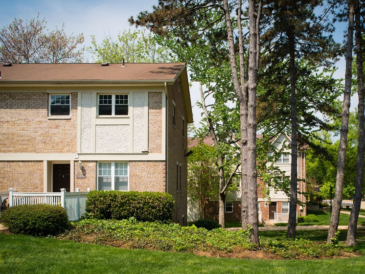 Exterior of Amberleigh apartments surrounded by tall trees and greenery in Fairfax, Virginia 22031