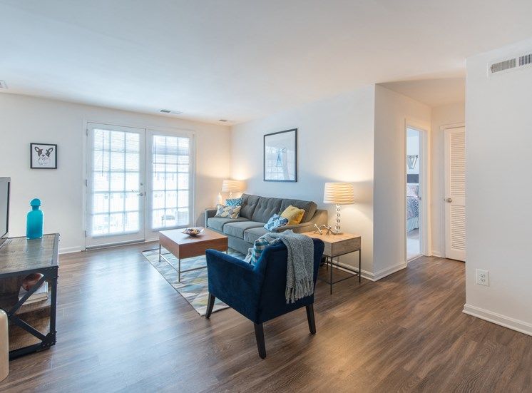 Spacious living room area with french doors leading to private balcony/patio at Amberleigh apartments in Fairfax, Virginia 22031