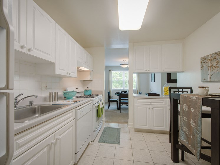 L-shaped kitchen with white cabinets, refrigerator, dishwasher at Amberleigh apartments in Fairfax, Virginia 22031