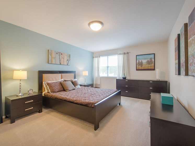Spacious, brightly lit bedroom with window, ceiling light, and carpeting at Amberleigh apartments in Fairfax, Virginia 22031