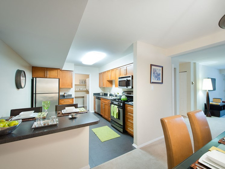 View of dining area and kitchen with breakfast bar at Amberleigh apartments in Fairfax, Virginia 22031