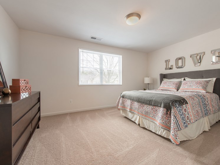 Brightly lit, spacious bedroom with window and carpeting at Amberleigh apartments in Fairfax, Virginia 22031