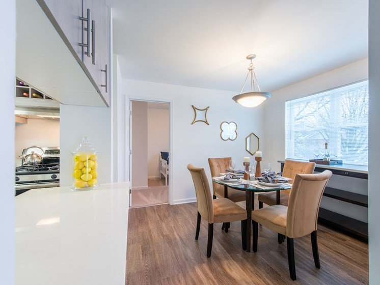 View of dining area with wood flooring, large window, ceiling fan, and next to kitchen breakfast bar at Amberleigh apartments in Fairfax, Virginia 22031
