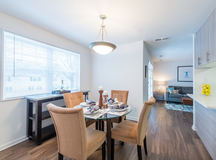 Open concept floor plan of dining area with ceiling light, wood flooring, large window at Amberleigh apartments in Fairfax, Virginia 22031