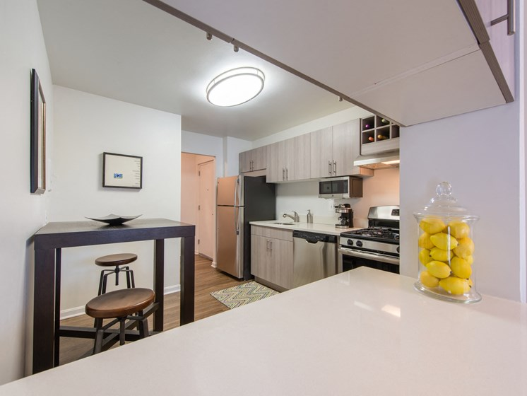 Upgraded fully-equipped kitchen with stainless steel appliances, breakfast bar, and wood flooring at Amberleigh apartments in Fairfax, Virginia 22031