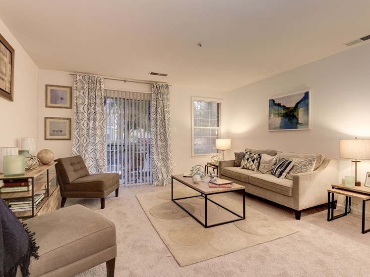 Spacious living room area with carpeting, window, and sliding glass door into private patio at The Edgemoore apartments in Alexandria, VA 22315