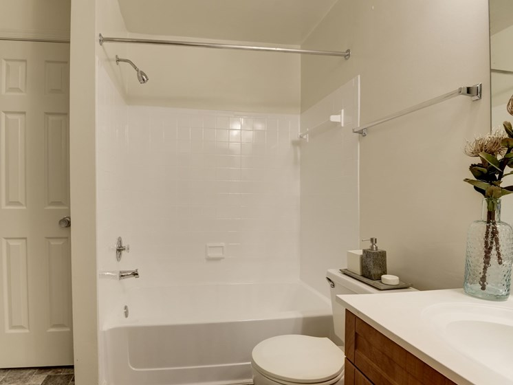 Bathroom featuring bathtub, sink with storage cabinets, towel bar at The Edgemoore apartments in Alexandria, VA 22315