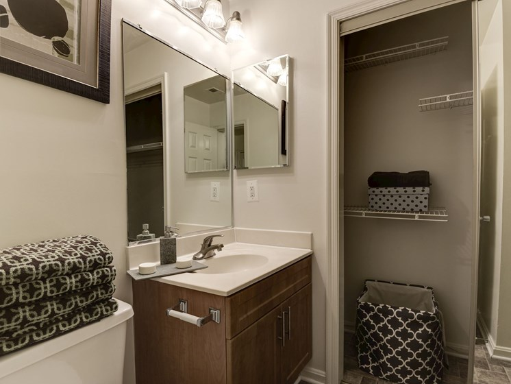 Half bathroom with extra storage closet, sink area with cabinets, at The Edgemoore apartments in Alexandria, VA 22315