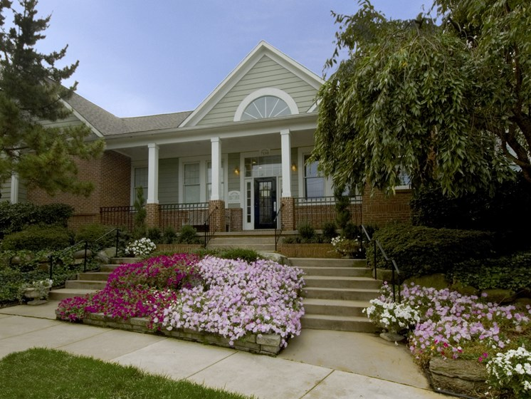 Exterior of clubhouse with front patio area and flower garden at The Edgemoore apartments in Alexandria, VA 22315