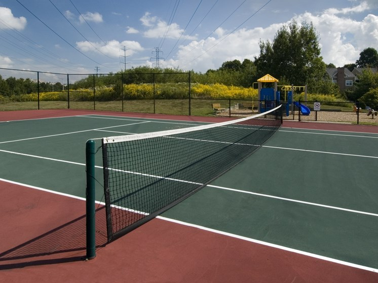 Professional-sized tennis court with playground in the background, at The Edgemoore apartments in Alexandria, VA 22315