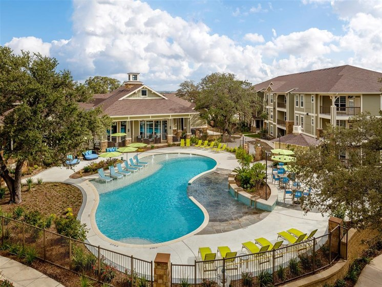 Aerial fenced in pool view with in and poolside seating surrounded by apartments, clubhouse and lush landscape
