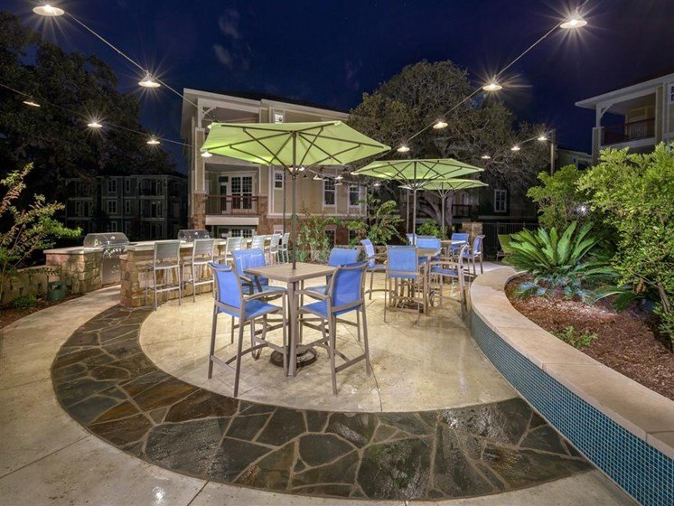 Nighttime BBQ grill patio with bar and high top umbrella covered seating