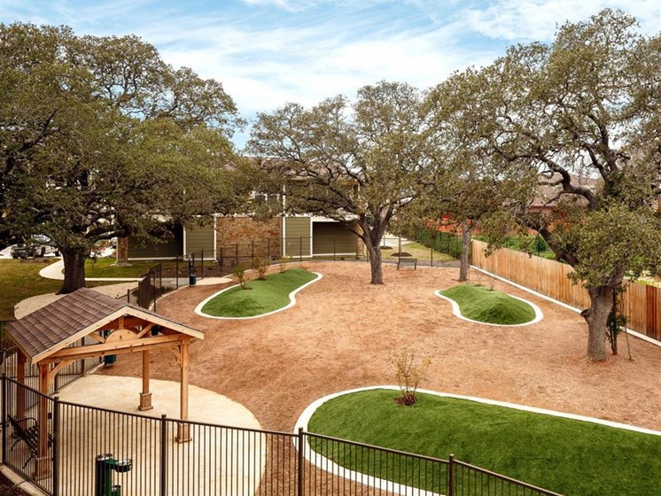 Aerial view of fenced in dog park with shaded gazebo and shade trees