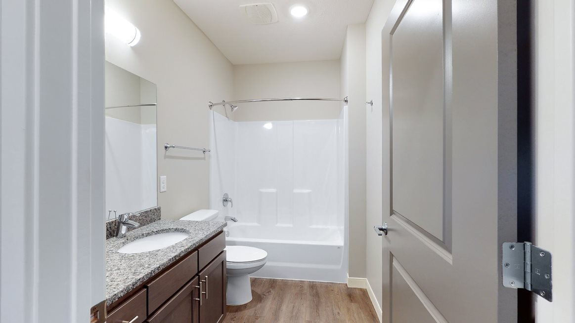 The 2 bedroom Marigold with den floor plan features a spaciou bathroom with granite vanity top and a tub/shower.