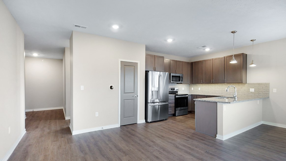 The 2 bedroom Marigold with den floor plan at WH Flats features an stainless steel appliances, granite countertops and large peninsula.