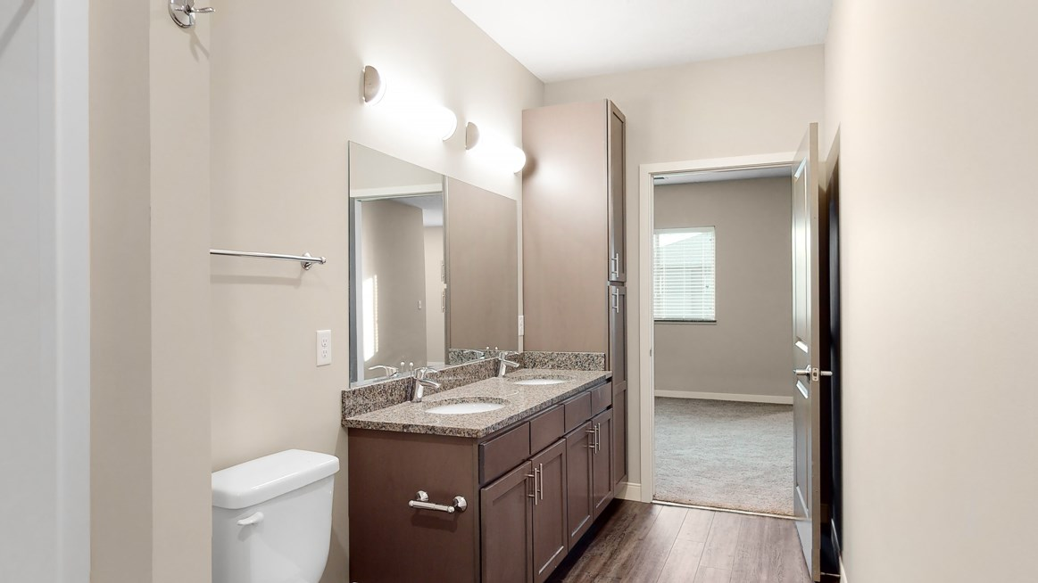 The master bathroom in the Marigold with den floor plan features dual vanity with large shower.