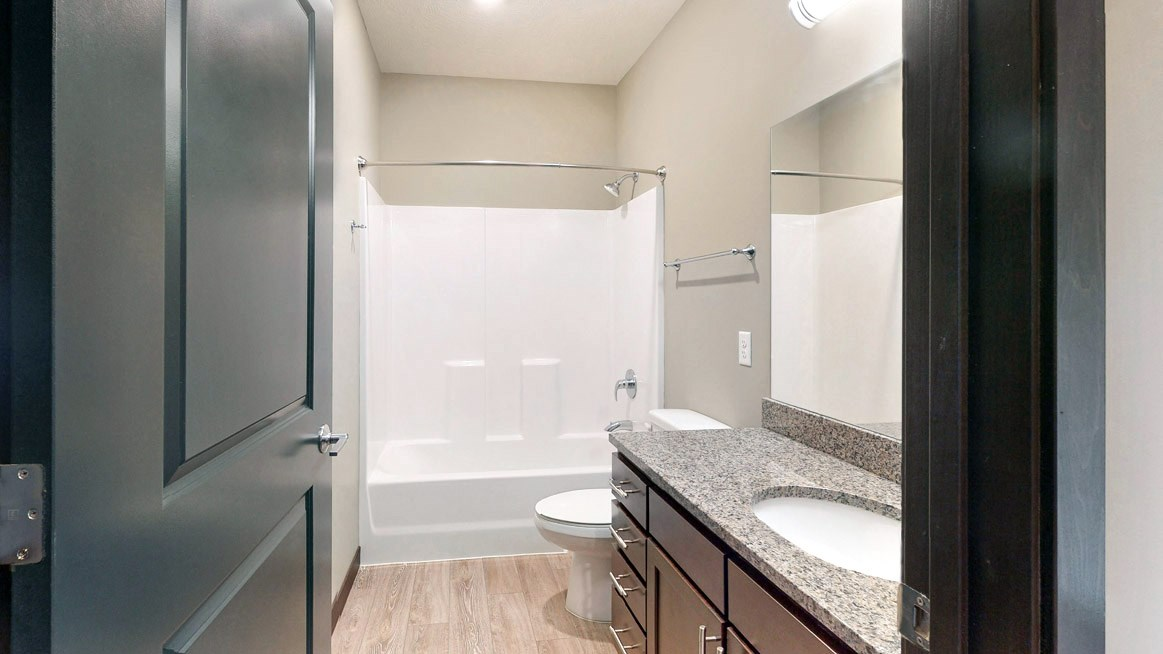 The 2 bedroom Snowdrop with den floor plan features a spacious bathroom with granite vanity top and a tub/shower.