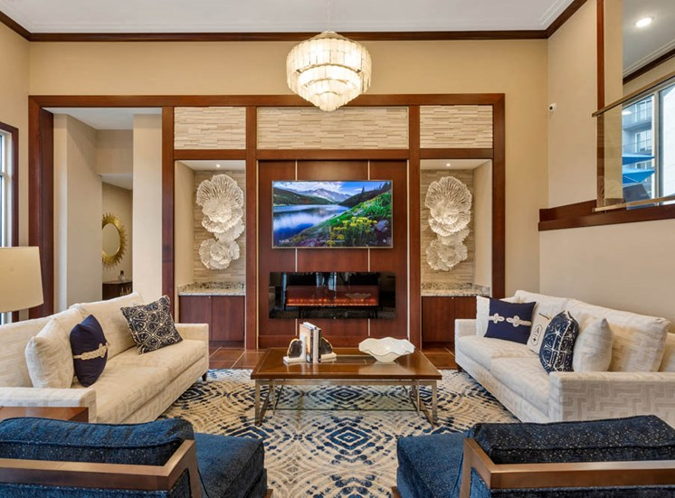 Luxury community space with a fireplace and television