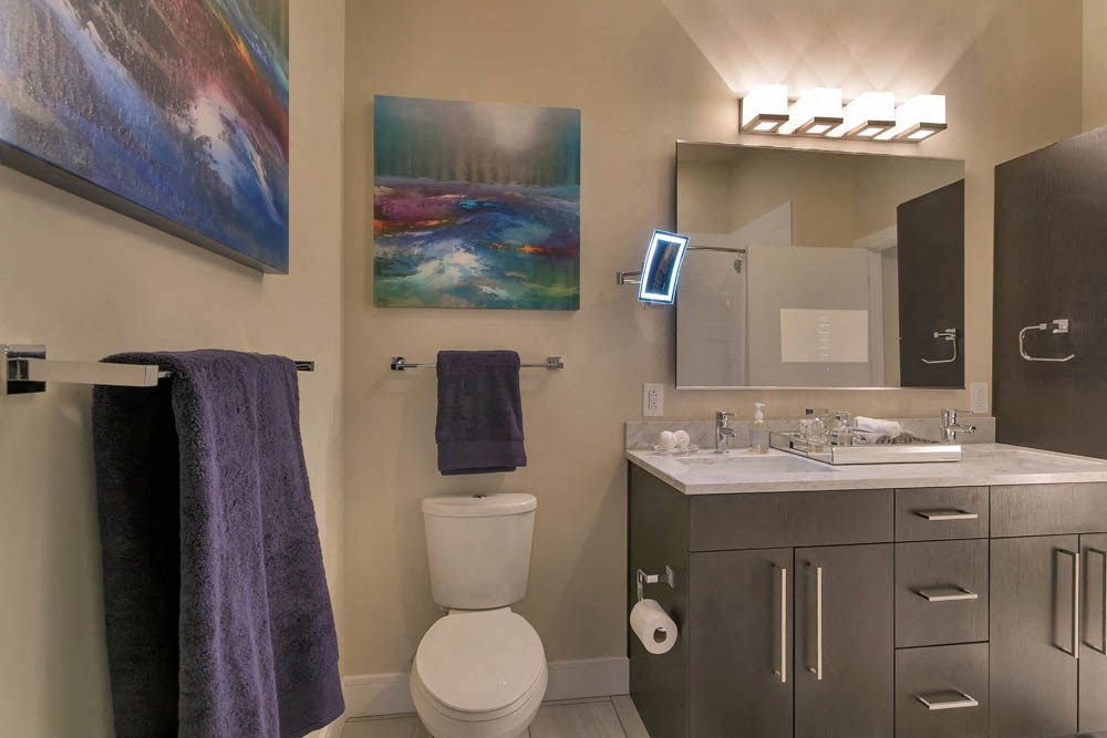 Gorgeous bathroom space with extensive storage space and bright finishes